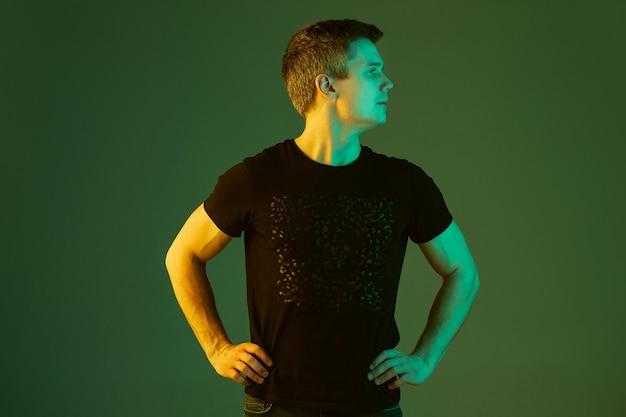 Olhando para o lado. retrato do homem caucasiano isolado no fundo verde do estúdio em luz de néon. lindo modelo masculino de camisa preta. conceito de emoções humanas, expressão facial, vendas, anúncio.
