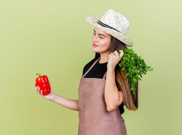 Olhando para o lado satisfeito, a linda garota jardineira de uniforme usando chapéu de jardinagem segurando pimenta com coentro isolado em fundo verde oliva