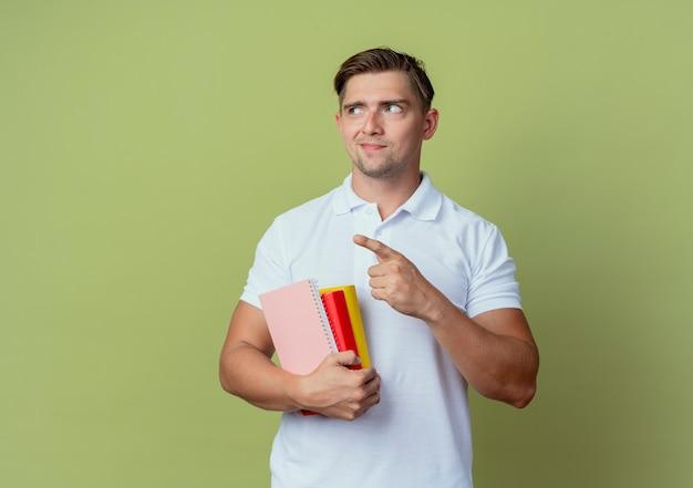 Olhando para o lado satisfeito, jovem bonito estudante do sexo masculino segurando livros e pontos ao lado isolados sobre fundo verde oliva