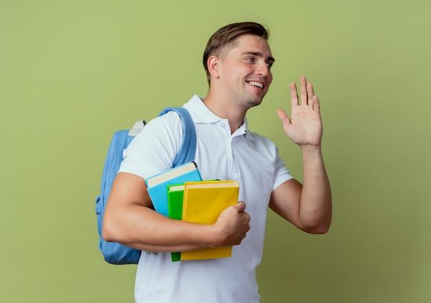 Olhando para o lado satisfeito, jovem bonito estudante do sexo masculino usando uma bolsa de costas segurando livros e levantando a mão isolado sobre fundo verde oliva