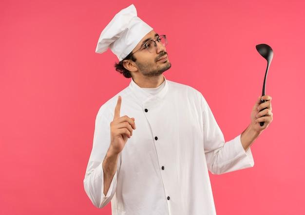 Olhando para o lado satisfeito, jovem cozinheiro vestindo uniforme de chef e óculos segurando uma concha e apontando para cima