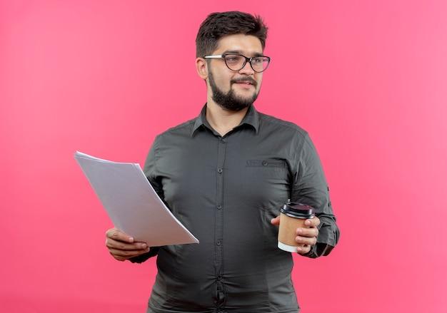 Olhando para o lado satisfeito, jovem empresário usando óculos, segurando um papel e uma xícara de café isoladas no fundo rosa