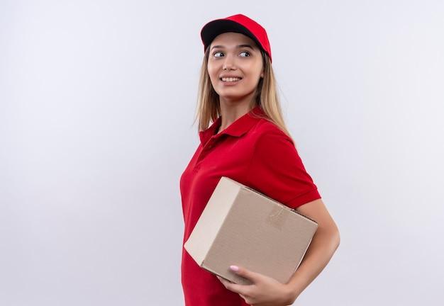 Olhando para o lado sorridente jovem entregadora vestindo um uniforme vermelho e boné segurando uma caixa isolada no fundo branco com espaço de cópia