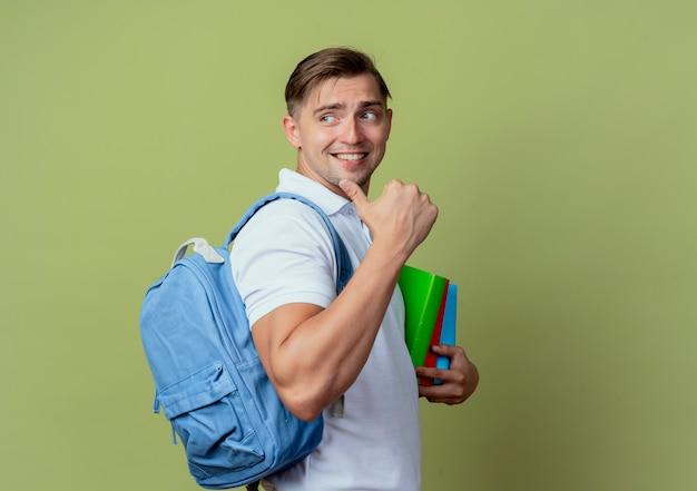 Olhando para o lado, sorrindo, jovem bonito estudante do sexo masculino usando uma bolsa de costas segurando livros e pontos ao lado, isolados na parede verde oliva