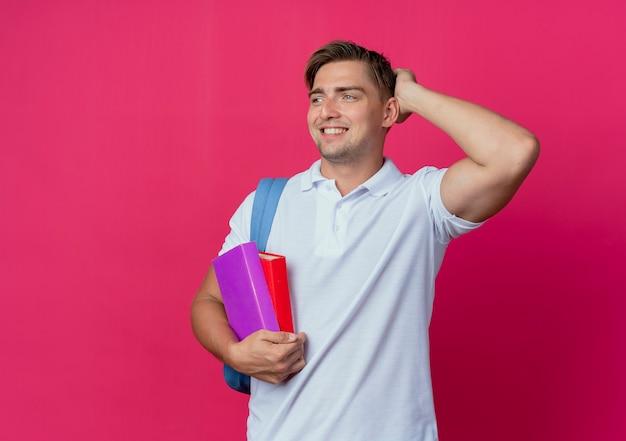 Olhando para o lado, sorrindo, jovem bonito estudante do sexo masculino usando uma bolsa nas costas segurando livros e colocando a mão na cabeça