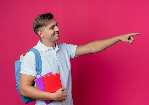 Olhando para o lado sorrindo, jovem bonito estudante do sexo masculino usando uma bolsa nas costas segurando livros e pontas ao lado