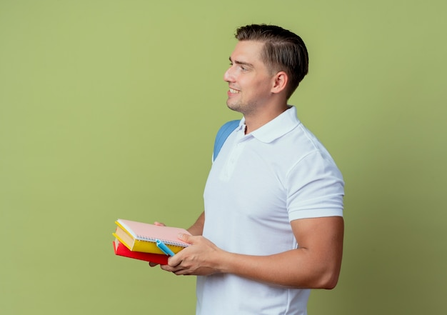 Olhando para o lado, sorrindo, jovem bonito estudante do sexo masculino usando uma bolsa nas costas segurando livros isolados sobre fundo verde oliva