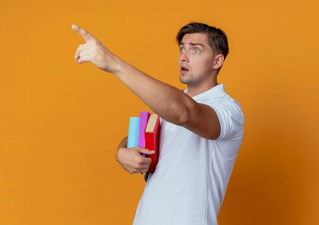 Olhando para o lado, surpreendeu o jovem bonito estudante do sexo masculino usando uma bolsa de costas segurando livros e pontos ao lado isolados em um fundo laranja