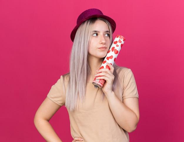 Olhando para o lado, uma jovem linda com um chapéu de festa segurando um canhão de confete isolado na parede rosa