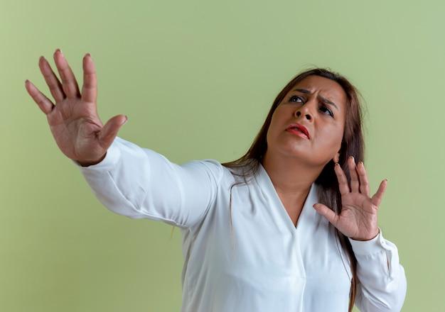 Olhando para o lado, uma mulher caucasiana de meia-idade, insatisfeita, mostrando um gesto de parar
