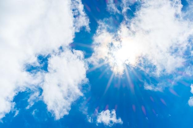 Olhando para o raio de sol por trás da nuvem com clarão de luz e céu azul