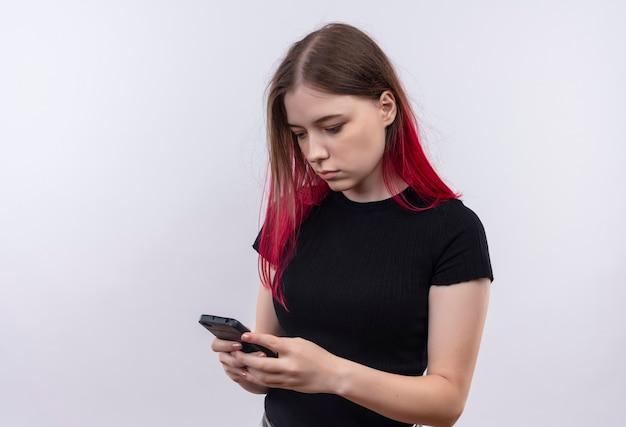 Olhando para o telefone, jovem e linda mulher vestindo uma camiseta preta para discar o número na parede branca isolada