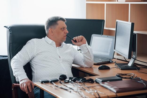 Olhando para os diagramas. o examinador de polígrafo trabalha no escritório com seu equipamento detector de mentiras