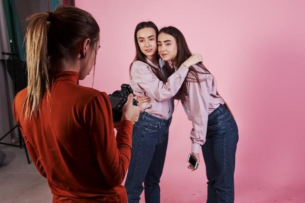Olhando para os resultados. imagem de duas meninas que abraçam cada uma e são fotografadas pelo operador de câmera feminino no estúdio