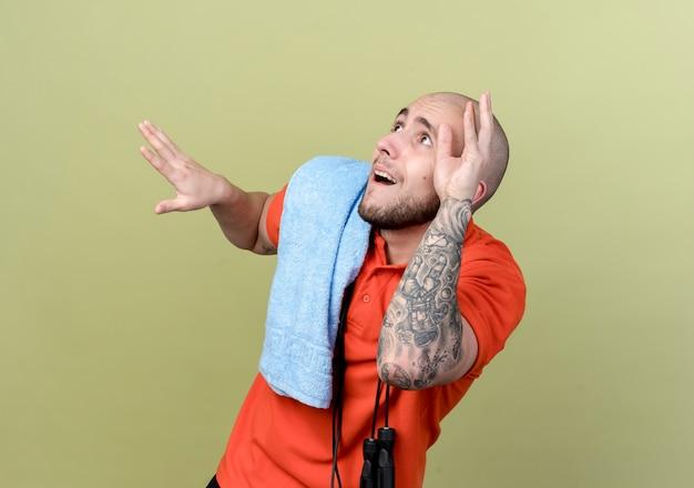 Olhando para um jovem desportivo assustado com uma toalha e pular corda no ombro, isolada na parede verde oliva