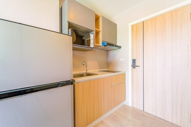 Olhando para uma pequena cozinha vazia com fogão, geladeira e armários