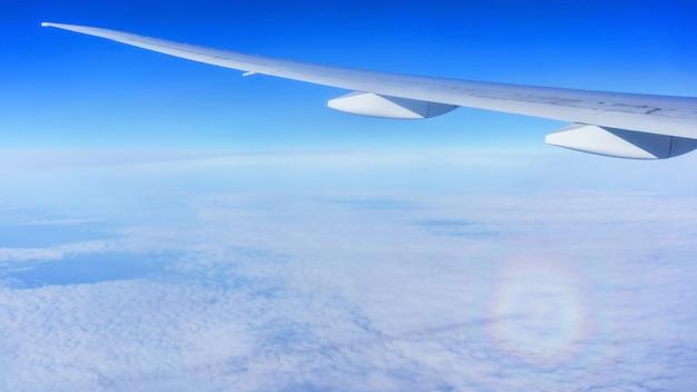 Olhando pela janela do avião, vendo um fenômeno óptico atmosférico associado à refração da luz do sol abaixo da asa do avião, nuvens brancas e céu azul