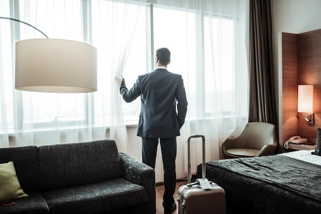 Olhando pela janela. próspero empresário de sucesso usando terno escuro, olhando pela janela de seu hotel