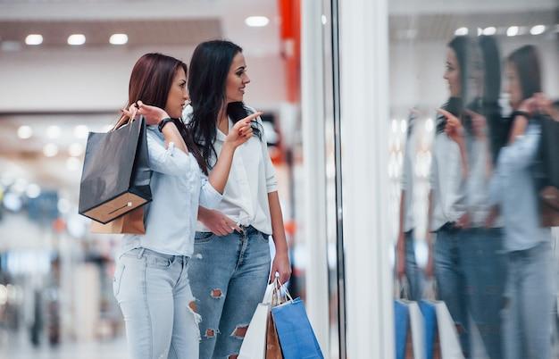 Olhando pelo vidro. duas jovens fazem compras juntas no supermercado.