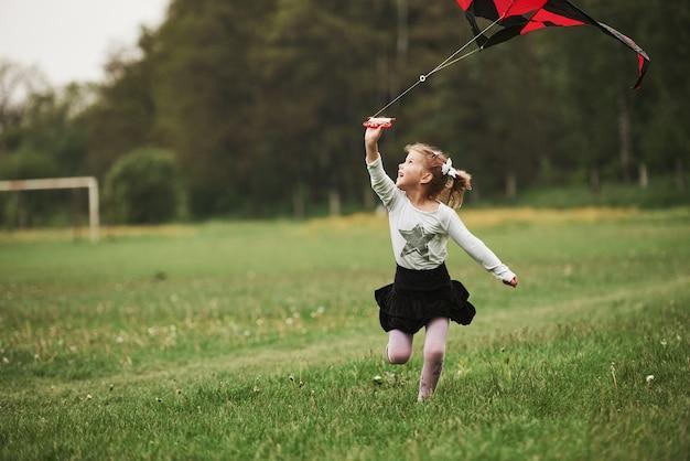 Olhando pra cima. tempo incrível. garota feliz com roupas casuais, correndo com a pipa no campo. natureza bela