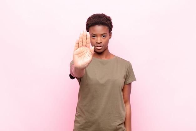 Olhando sério, popa, descontente e com raiva mostrando a palma da mão aberta, fazendo o gesto de parada
