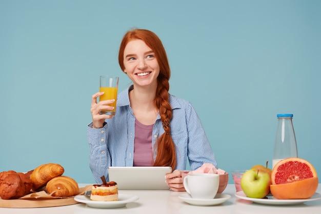 Olhando sonhadoramente para o canto superior direito, linda mulher ruiva e sorridente bebendo suco de laranja