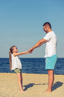 Olhando um para o outro e sorrindo, de pé à beira-mar ensolarado