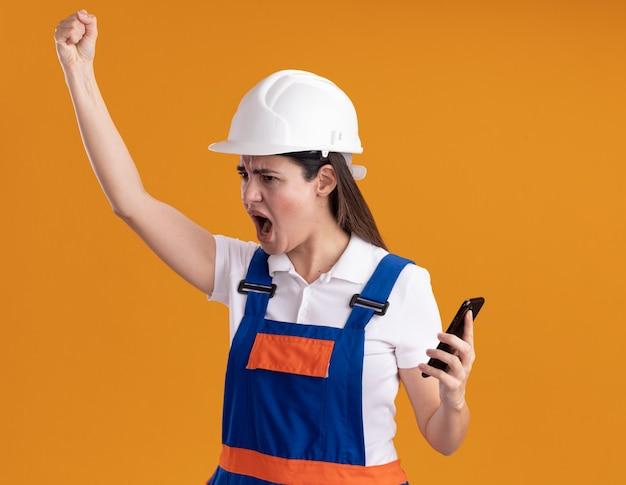Olhando zangado para o lado, jovem construtora de uniforme levantando o punho segurando o telefone isolado na parede laranja