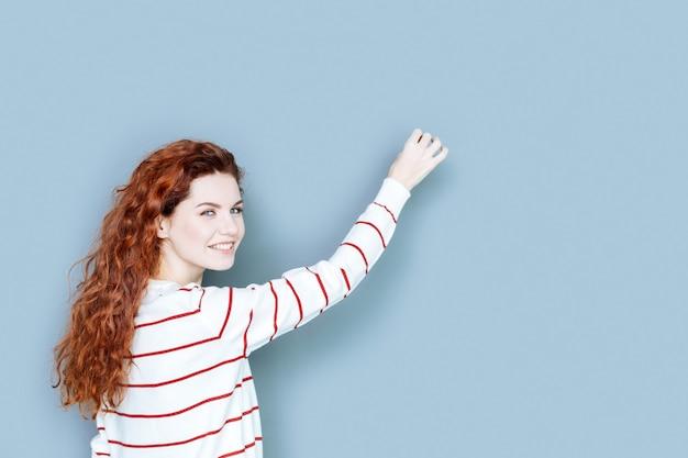 Olhar amigável. mulher jovem, positiva e encantada, virando-se para você e sorrindo enquanto escreve na parede