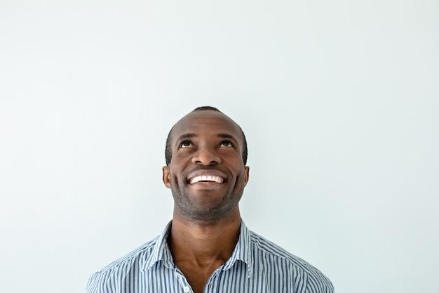 Olhar bem sucedido. homem afro-americano bonito alegre sorrindo em pé contra um fundo branco