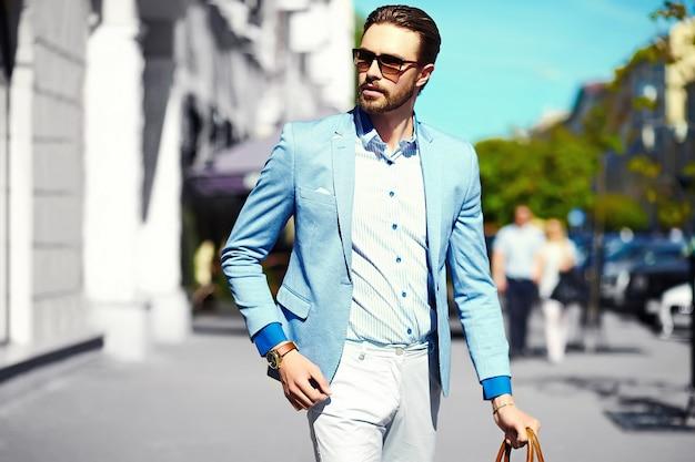 Olhar de alta moda. modelo elegante jovem feliz confiante empresário bonito no estilo de vida de pano de terno na rua em óculos de sol