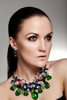 Olhar de alta moda. retrato de closeup glamour do modelo morena caucasiano mulher jovem e bonita com cabelo saudável com pele limpa perfeita e joia de acessório azul