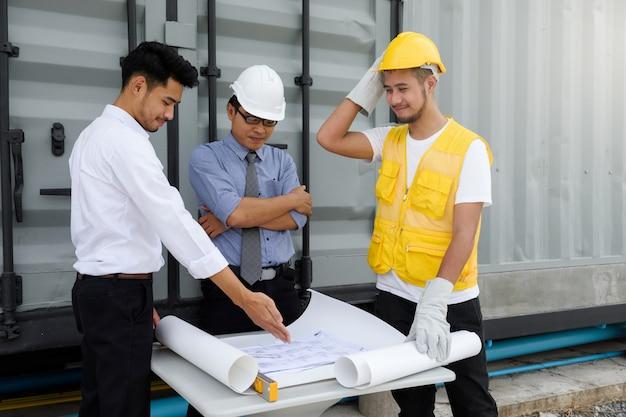 Olhar de equipe de engenheiro no blueprint de construção