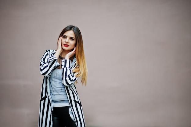Olhar de mulher elegante com paletó listrado preto e branco, calças de couro posando contra a parede. conceito de menina da moda.