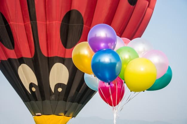 Olhar grande do balão de ar quente em pouco balão no céu.