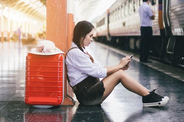 Olhar grávido da mulher asiática do curso no smartphone com uma mala de viagem vermelha na estação de trem.