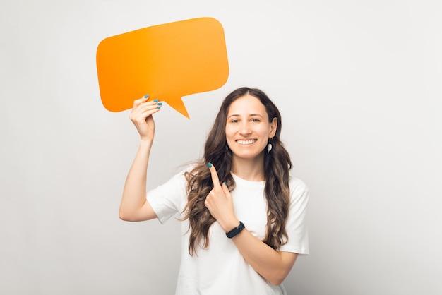 Olhar. jovem mulher de cabelos compridos está segurando um balão de fala laranja.