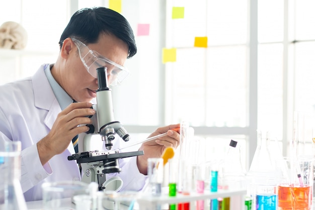 Olhar masculino asiático do cientista através do microscópio no laboratório.