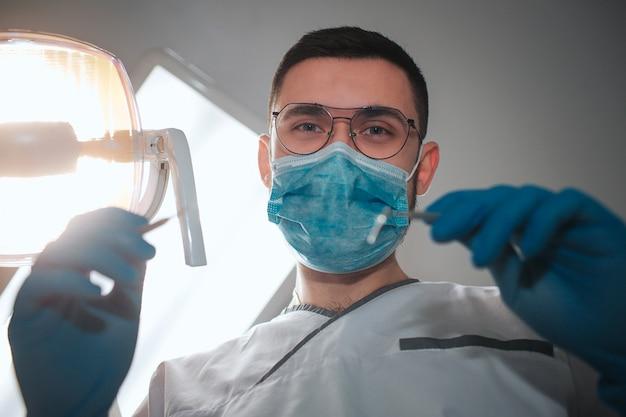 Olhar masculino novo do dentista na câmera. ele usa rob branco e máscara azul. cara segura o equipamento de dentes para tratamento. a lâmpada está ligada. sala de odontologia.