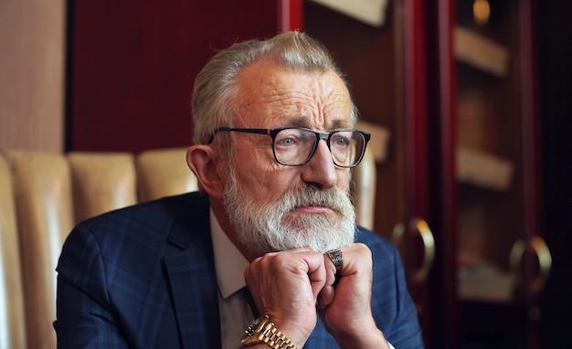 Olhar pensativo e sério do empresário, o proprietário da empresa, elegantemente vestido com um terno elegante, foto dentro da sala, escritório.