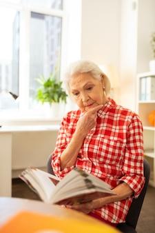 Olhar pensativo. mulher séria e idosa tocando seu queixo enquanto lê um livro