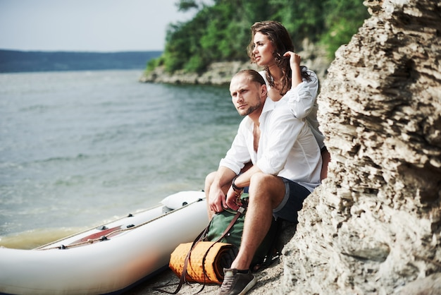 Olhar pensativo. turistas satisfeitos com a viagem que fazem no fundo de árvores perto do barco.