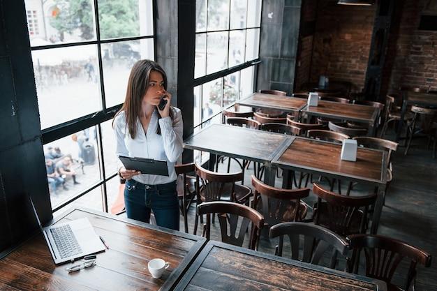 Olhar preocupado. mulher de negócios com roupas oficiais está dentro de casa no café durante o dia.