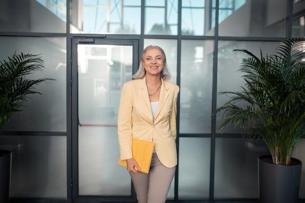 Olhar satisfeito. mulher de negócios sênior caucasiana satisfeita com uma pasta de papel amarela em pé no prédio de escritórios e olhando para a frente