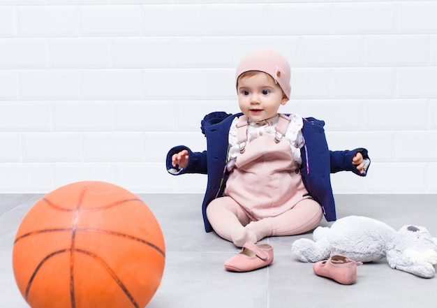 Olhar urbano bebê com bola de basquete
