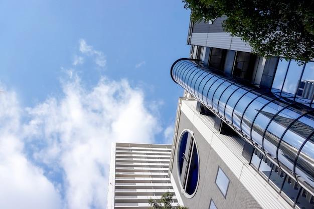 Olhe acima a vista e a colheita do prédio de escritórios no fundo brilhante do céu azul. com espaço para textos