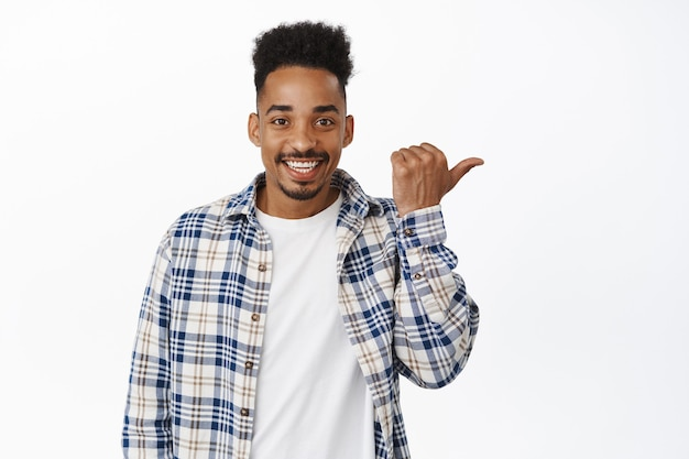 Olhe ali. homem afro-americano bonito e feliz sorrindo, apontando para o logotipo da venda, mostrando o texto promocional do desconto, convidar para a loja, seguir o link, em pé no branco