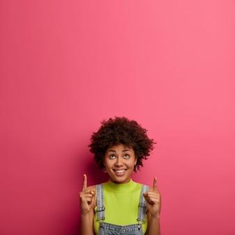 Olhe ali. mulher bastante satisfeita tem expressão feliz, promove produtos, indica acima, diz sua promoção aqui, demonstra espaço de cópia na parede rosa para seu conteúdo de publicidade. liquidação de primavera