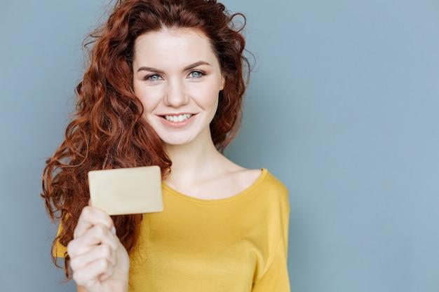 Olhe aqui. mulher alegre e feliz sorrindo e olhando para você enquanto mostra seu cartão