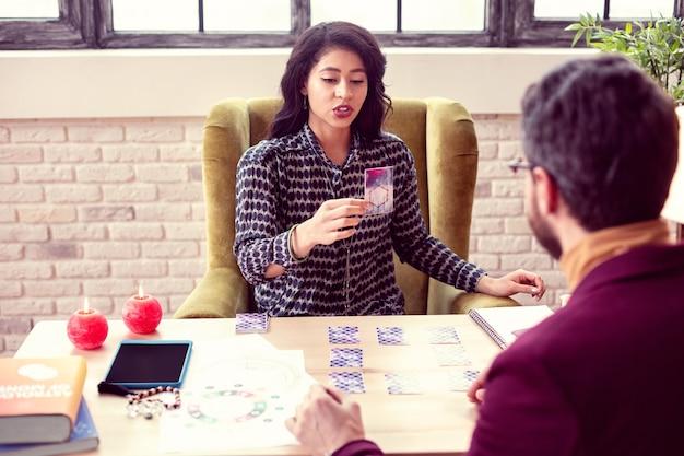 Olhe aqui. mulher bonita e inteligente sentada em frente ao cliente enquanto mostra um cartão para ele